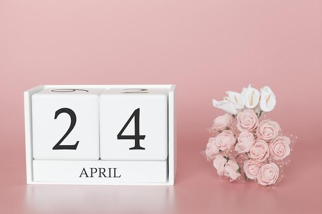 24 avril. jour 24 du mois. cube de calendrier sur rose moderne