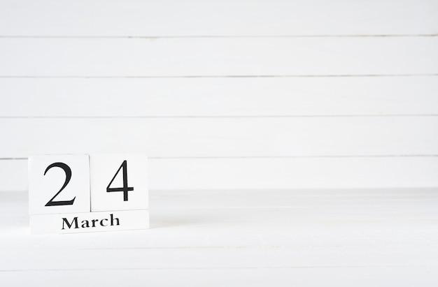 24 mars, jour 24 du mois, anniversaire, anniversaire, calendrier de bloc en bois sur un fond en bois blanc avec espace de copie du texte.
