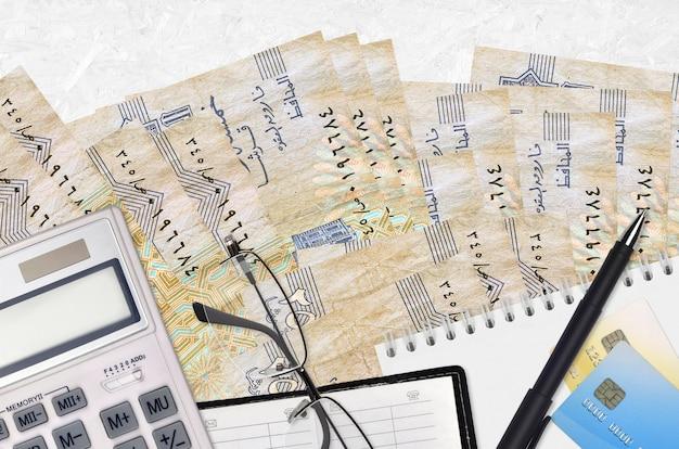25 factures de piastres égyptiennes et calculatrice avec lunettes et stylo. concept de saison de paiement des impôts ou solutions d'investissement. planification financière ou paperasse comptable