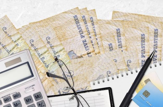 25 factures de piastres égyptiennes et calculatrice avec lunettes et stylo