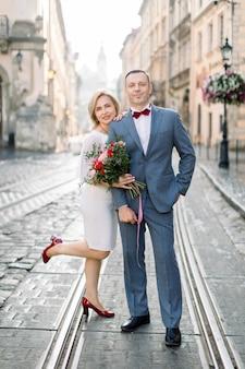 25e anniversaire de mariage. portrait en plein air d'un charmant couple d'âge mûr homme et femme vêtus d'élégants vêtements de luxe, posant ensemble sur le chemin de fer du tramway dans l'ancien centre-ville