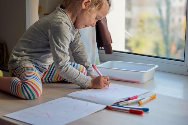 3 ans fille arts créatifs. l'enfant prend une image. jardin d'enfants et école maternelle fermés pendant covid-19, éducation en ligne, enseignement à domicile. petite fille étudie à la maison, apprentissage à domicile.