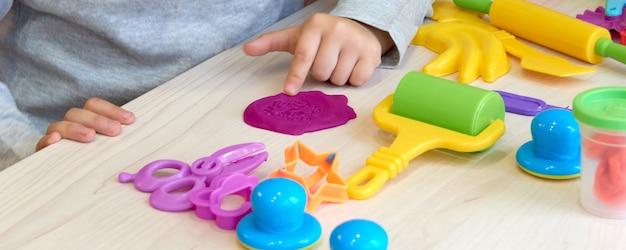 3 ans fille arts créatifs. mains d'enfant jouant avec de la pâte à modeler d'argile colorée. auto-isolement covid-19, éducation en ligne, enseignement à domicile. petite fille étudie à la maison, apprentissage à domicile.
