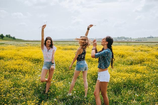 3 belle fille hippie dans un champ de fleurs jaunes