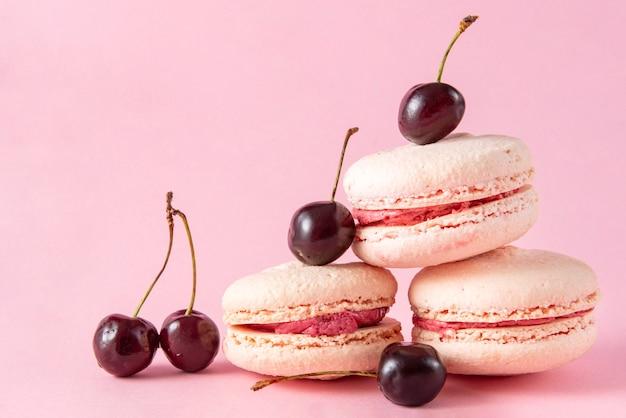 3 macarons français beiges aux cerises à la crème rose sur une surface rose, biscuits