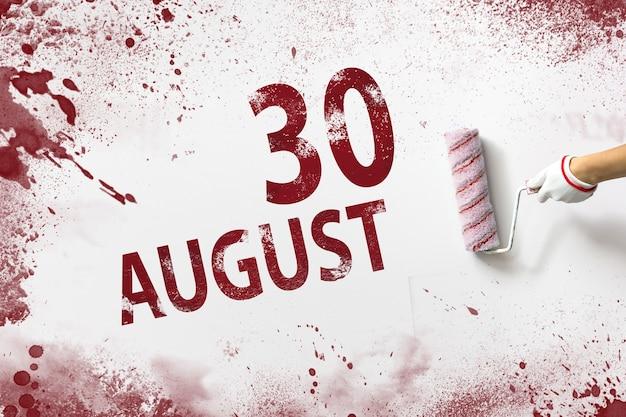30 août. jour 30 du mois, date du calendrier. la main tient un rouleau avec de la peinture rouge et écrit une date calendaire sur fond blanc. mois d'été, concept de jour de l'année.