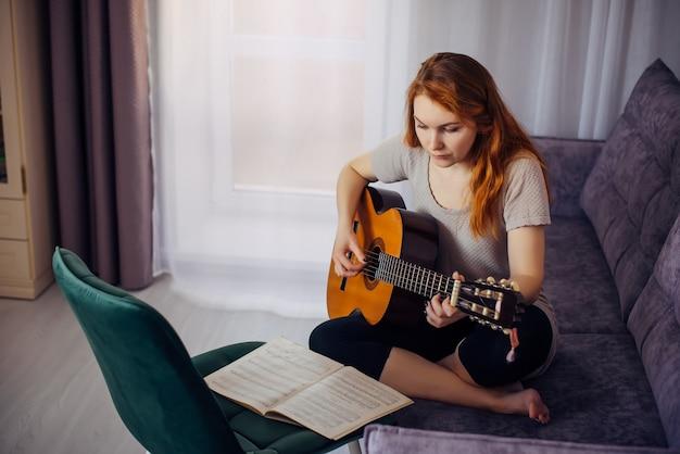 30 femme jouant de la guitare, assise sur le canapé à l'intérieur de la maison. jolie jeune fille apprenant à jouer de la guitare avec des partitions. mode de vie, passe-temps, loisirs, concept de développement des talents.
