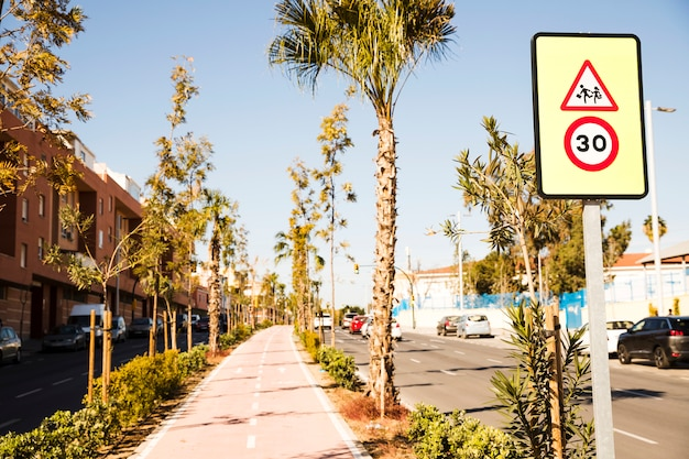 30 panneau de limitation de vitesse sur la rue et la piste cyclable avec des arbres verts