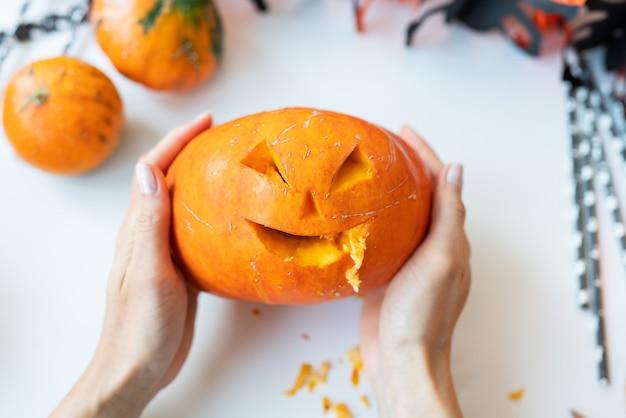 31 octobre. fête d'halloween. la jeune fille tient le visage sculpté d'une citrouille dans ses mains. vue d'en-haut.