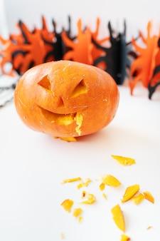 31 octobre. fête d'halloween. le visage sculpté d'une citrouille sur fond orange et noir.