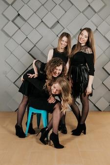 4 belles filles en robes noires posant pour la caméra contre un mur gris, souriant de bonne humeur et faisant des gestes.