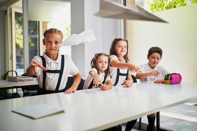 4 enfants lançant des avions en papier à l'intérieur d'une salle de classe à l'école