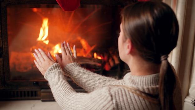 4 images k de jeune femme en pull se réchauffant et se frottant les mains à la cheminée en feu dans la maison