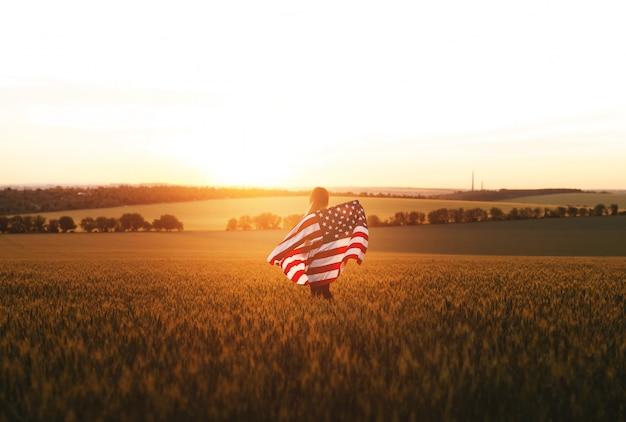 4 juillet. femme avec le drapeau américain en cours d'exécution dans un champ de blé au coucher du soleil. fête de l'indépendance, fête patriotique.