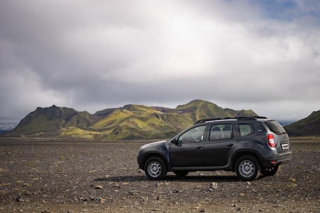 4x4 Voiture Garée Hors Route Sur Le Champ De Lave Noire Sur Le Chemin De La Région De Landmannalaugar, Islande. Photo Premium