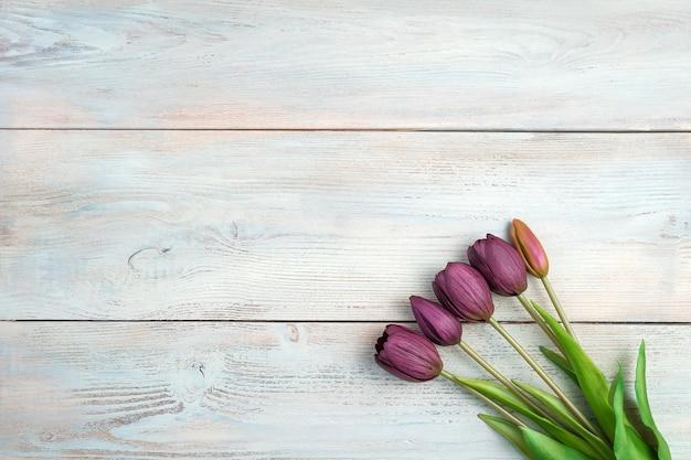 5 belles tulipes sur un fond en bois clair. vue de dessus avec espace pour copier.