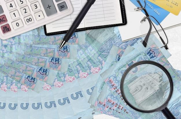 5 factures de hryvnias ukrainiennes et calculatrice avec lunettes et stylo.