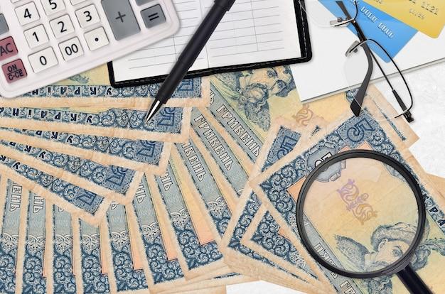 5 factures de hryvnias ukrainiennes et calculatrice avec lunettes et stylo