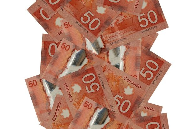 50 billets de dollars canadiens volant vers le bas isolés. de nombreux billets tombant avec espace copie blanche sur le côté gauche et droit