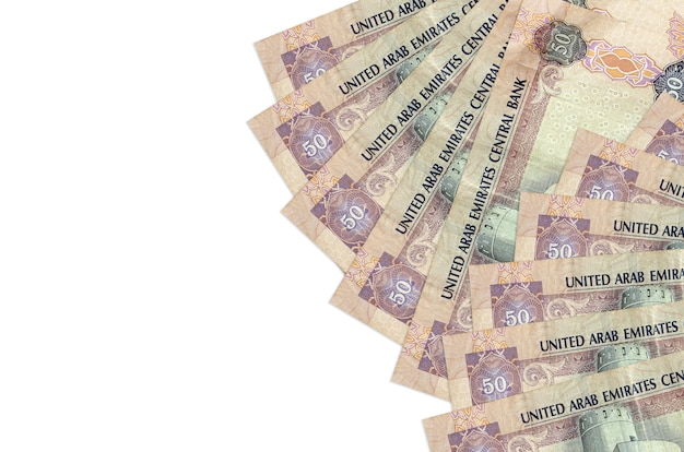 50 factures de dirhams des émirats arabes unis se trouve isolé sur un mur blanc avec espace de copie. mur conceptuel de vie riche. grande quantité de richesse en monnaie nationale