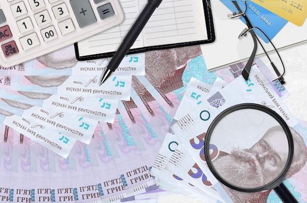 50 factures de hryvnias ukrainiennes et calculatrice avec lunettes et stylo