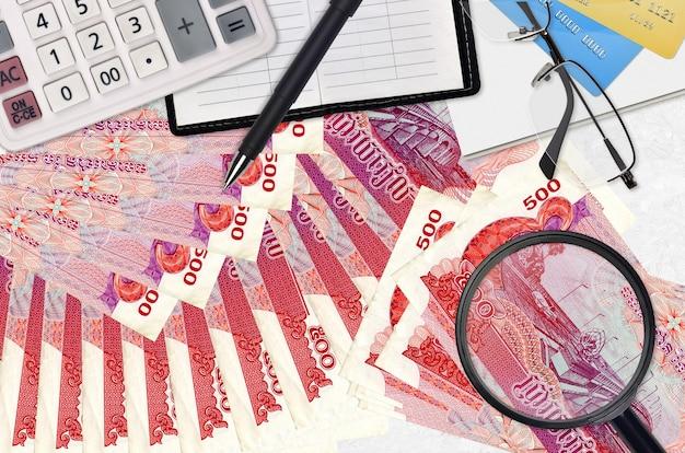 500 billets de riels cambodgiens et calculatrice avec lunettes et stylo