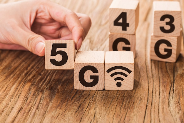 5g (5ème génération) réseau connectant la technologie future globale. changement de cube en bois à la main numéro 4g à 5g