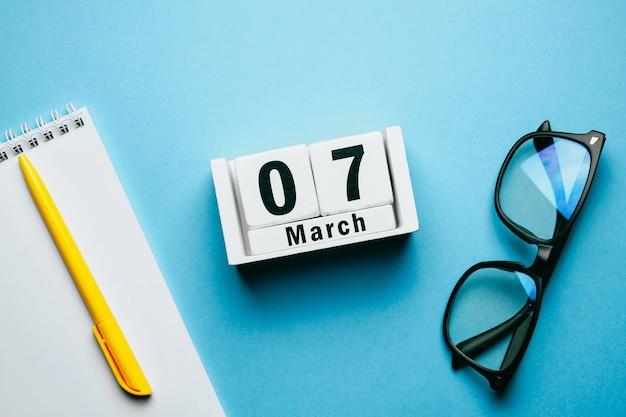 7 septième jour de mars sur le calendrier avec cahier, lunettes et stylo