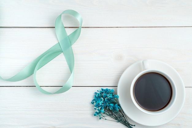 8 mars, fond festif avec une tasse de café et de fleurs sur fond clair.