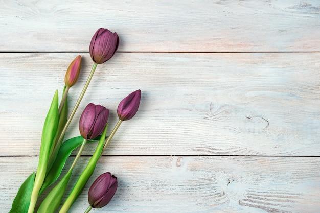 8 mars, fond festif avec des tulipes sur un fond en bois clair.