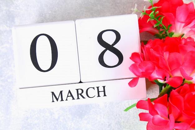 8 mars, journée internationale de la femme. calendrier perpétuel en bois et fleurs roses