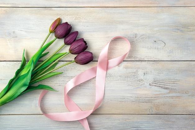 8 de ruban et un bouquet de tulipes sur fond clair. vue de dessus avec espace pour copier.