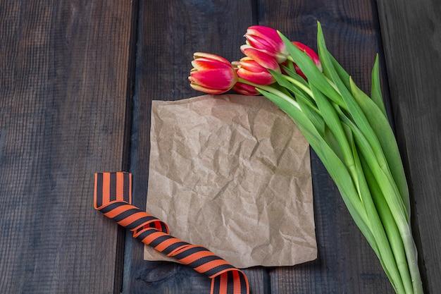 9 mai fond - modèle de carte de voeux vierge avec des tulipes rouges, ruban george et note papier sur le fond en bois. jour de la victoire ou concept de jour du défenseur de la patrie. vue de dessus, espace de copie pour le texte