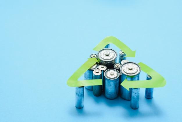 Aa usagés et élimination appropriée des piles toxiques pour l'environnement et le sol sur fond bleu
