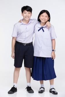 Aasian fille et garçon en uniforme d'étudiant sur gris