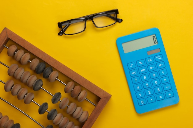 Abaque vintage et calculatrice, verres sur jaune.