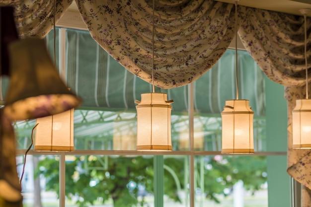 Abat-jour suspendus en forme de bidons de lait suspendus par fenêtre