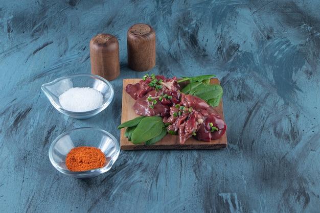 Abats de poulet sur une planche à côté de bols de sel et d'épices, sur la surface bleue.
