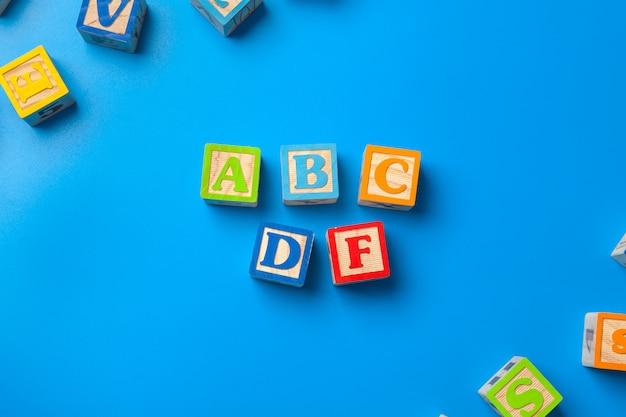 Abcdf. blocs d'alphabet coloré en bois sur table bleue