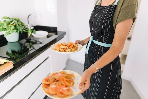 Abdomen d'une femme tenant deux assiettes avec des tranches de pâtes et de tomates