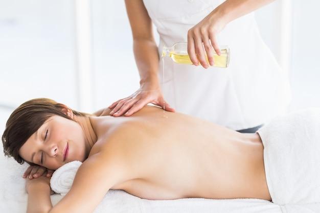 Abdomen de masseur verser de l'huile sur le dos de la femme