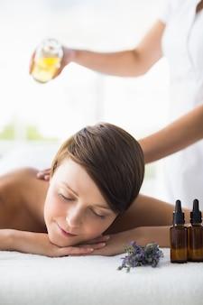 Abdomen de masseur verser de l'huile sur une femme