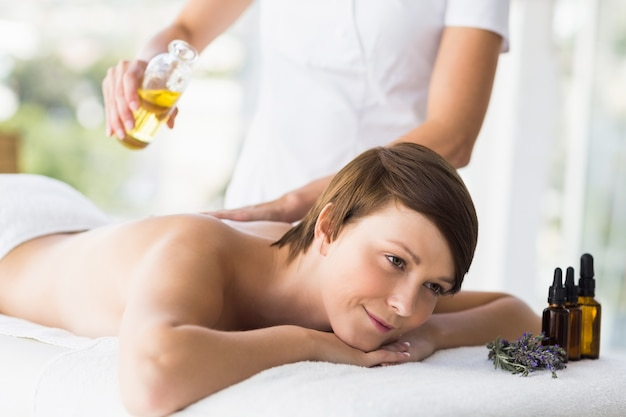 Abdomen de massuer verser de l'huile sur le dos de la femme