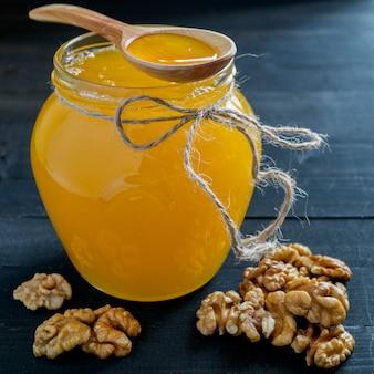 Abeille à miel dans un bocal avec une cuillère en bois.