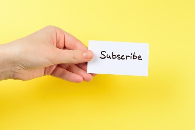 Abonnez-vous au texte sur une carte en main de femme sur une surface jaune.