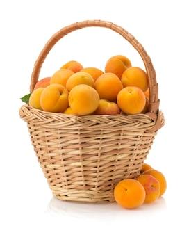Abricot dans le panier isolé sur une surface blanche