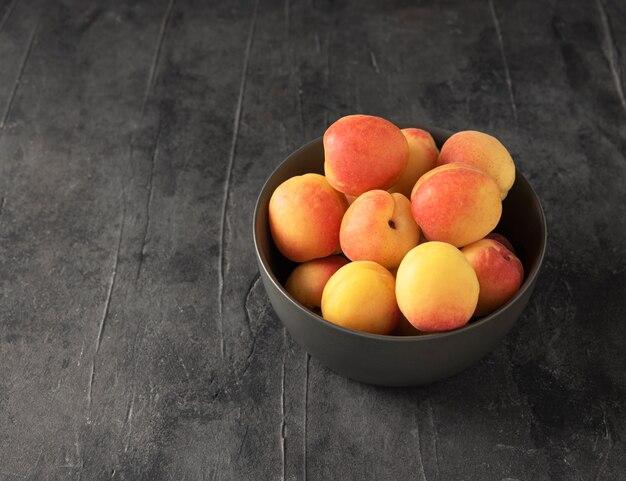 Abricot délicieux sucré sur bol gris table grise fruits frais d'été