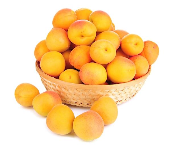 Abricot naturel frais dans le panier en osier isolé sur blanc