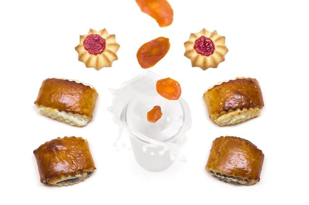 Abricot séché tombant dans un verre de lait avec des éclaboussures autour desquelles sont de savoureux biscuits