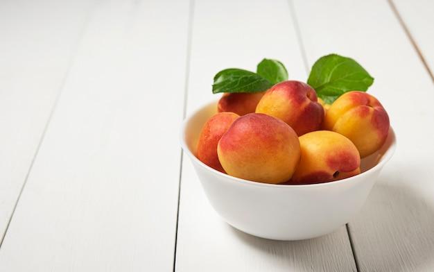 Abricot sucré délicieux sur bol sombre table en bois blanc fruits frais d'été